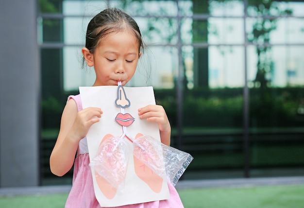 肺の模擬呼吸で吹いて遊ぶ少女。ヘルスケアの概念 Premium写真