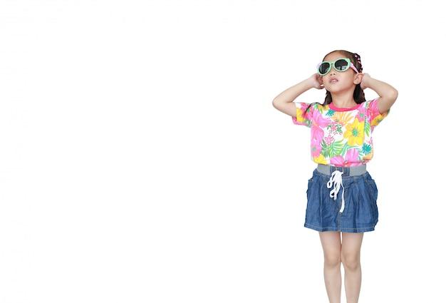 Милая маленькая азиатская девушка ребенк нося изолированное платье и солнечные очки лета цветков. готов к летним каникулам. Premium Фотографии