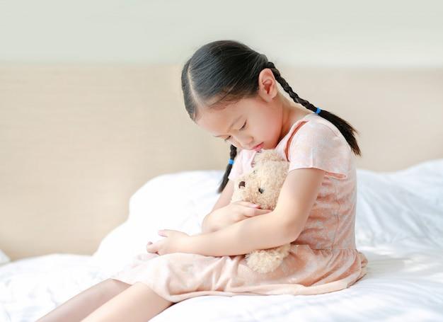 Мирная азиатская маленькая девочка, обнимая плюшевого мишку, сидя на кровати у себя дома Premium Фотографии