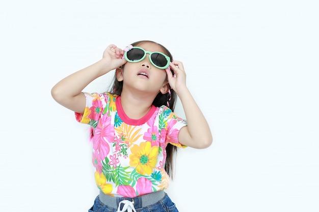 Красивая маленькая азиатская девушка ребенк нося платье и солнечные очки лета цветков смотря вверх изолированный на белизне. Premium Фотографии