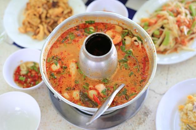 Тайский пряный суп томьям в горячем горшочке. Premium Фотографии