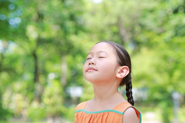 幸せなアジアの子供の肖像画は、自然からの新鮮な空気を吸うと庭で彼らの目を閉じます。 Premium写真