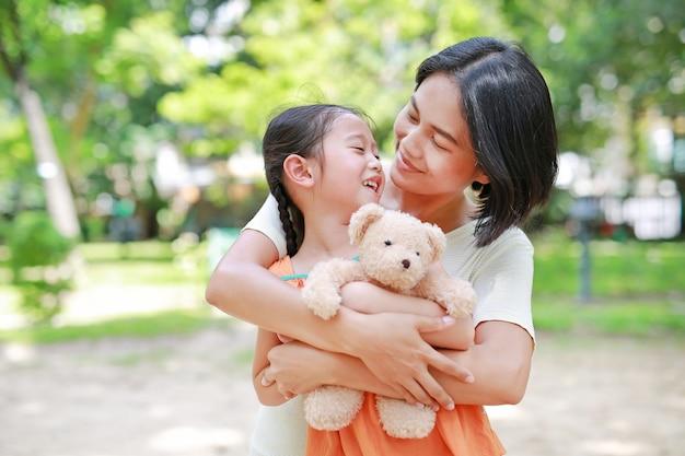 Счастливая мама обниматься дочь и обнимать куклу мишка в саду. Premium Фотографии