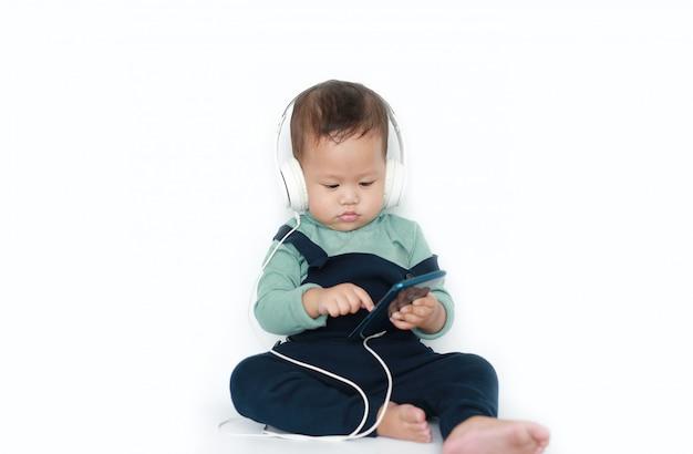 愛らしいアジアの小さな男の子は、スマートフォンでヘッドフォンで音楽を聴くことを楽しんでいます Premium写真