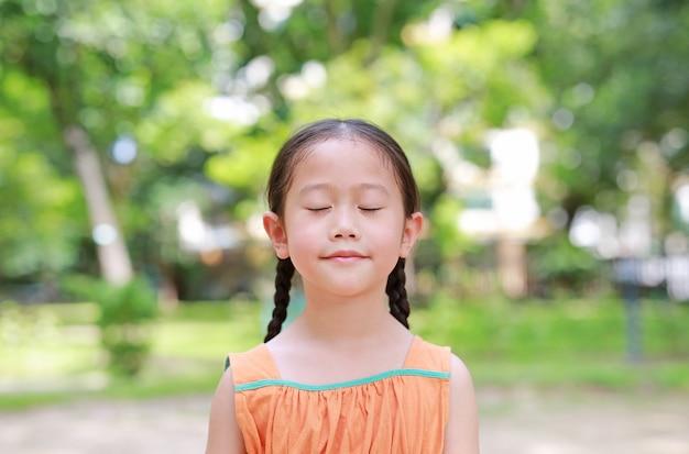 幸せなアジアの子供の肖像画は、自然からの新鮮な空気を吸い込んで庭で目を閉じます。子供の女の子をクローズアップ健康のために緑豊かな公園でリラックスします。 Premium写真