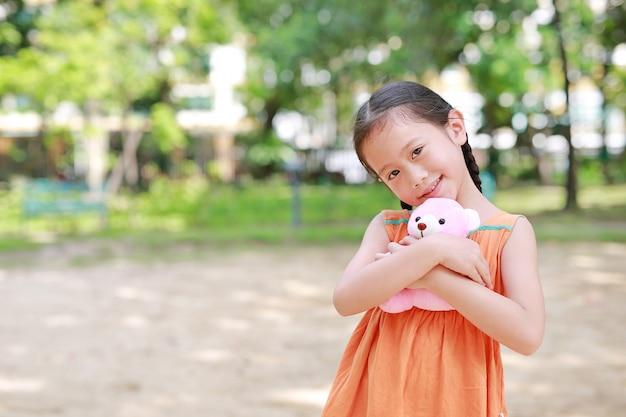 カメラ目線で庭でテディベアの人形を抱き締める愛らしい小さなアジアの子女の子。夏の公園で幸せな子供を閉じます。 Premium写真