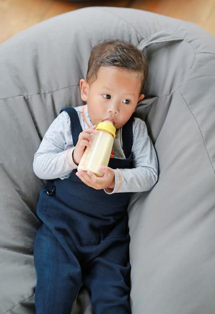 男の子の赤ちゃんを押しながらソファーに横になっているボトルからミルクを供給します。 Premium写真