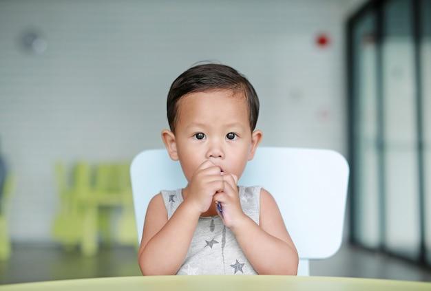 教室でチョコレートを食べる愛らしい小さなアジアの男の子。 Premium写真