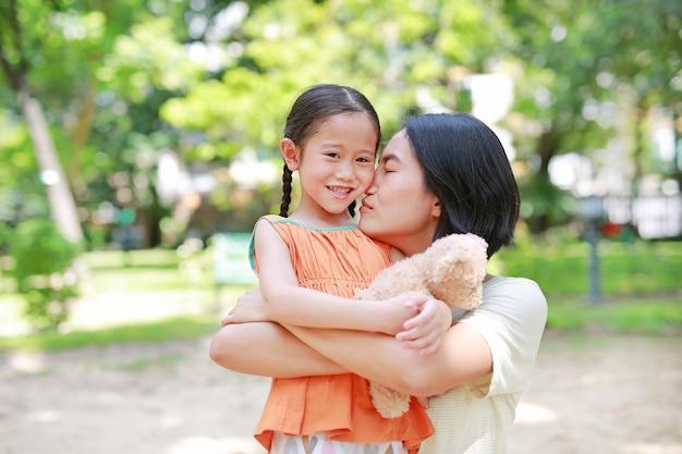 幸せなアジアの母の抱擁娘と庭でハグテディベア人形の肖像画。 Premium写真