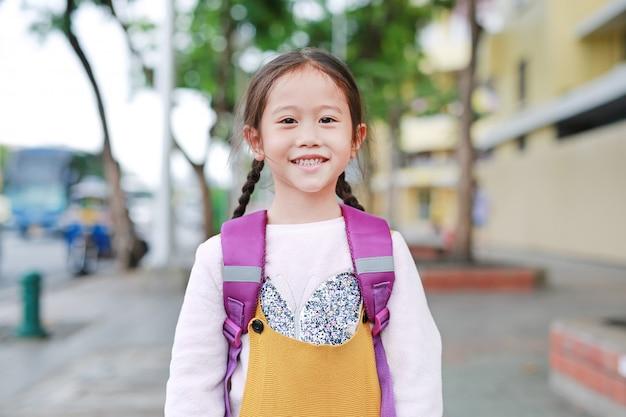 カバンと歩いて幸せなアジアの子供女の子 Premium写真