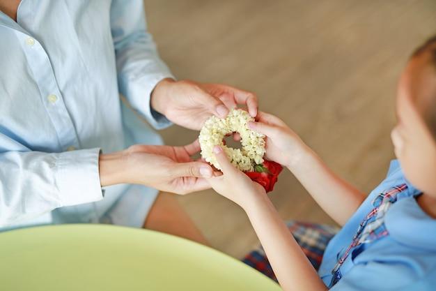 アジアの娘のクローズアップは敬意を払って、母にタイの伝統的なジャスミンの花輪を与える Premium写真
