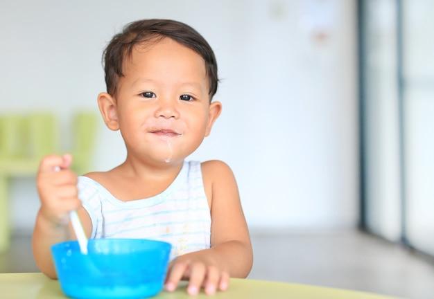Счастливый маленький азиатский мальчик ест хлопья с кукурузными хлопьями и молочными пятнами вокруг рта на столе Premium Фотографии