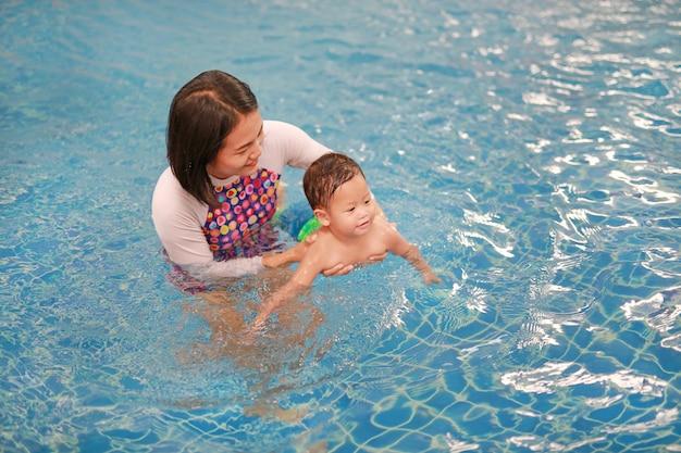 アジアの母親と男の子のプールでリラックス Premium写真