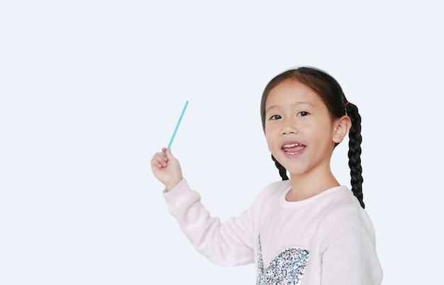 Усмехаясь маленькая азиатская девушка указывая вверх представляет что-то Premium Фотографии