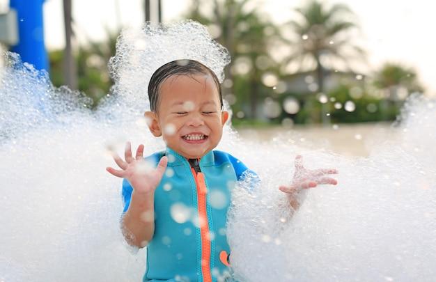屋外プールで泡パーティーで楽しんで笑って幸せな小さなアジア男の子の肖像画。 Premium写真