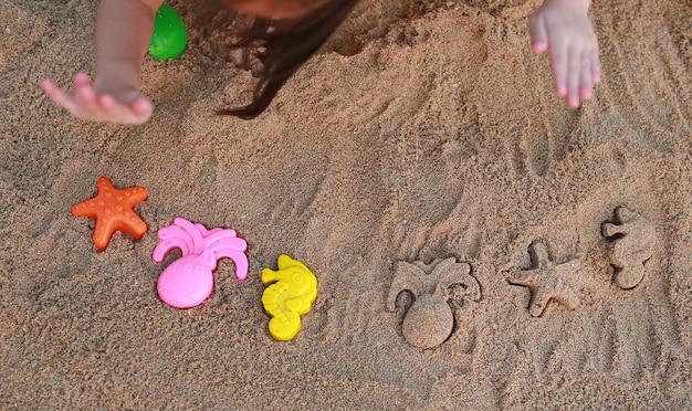 クローズアップの子供たちは、ビーチで形成された動物のブロックと砂を再生します。 Premium写真