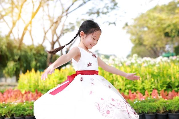 Счастливая азиатская девушка маленького ребенка танцуя и имея потеху в свежем цветочном саде. детские игры в парке на открытом воздухе. Premium Фотографии