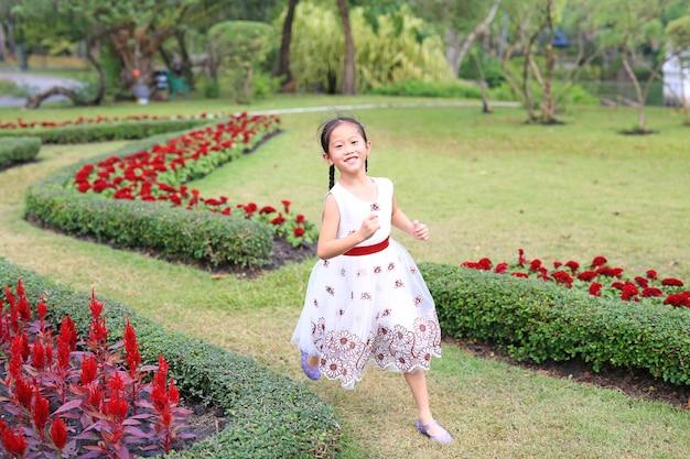 Счастливая азиатская маленькая девочка в белом платье бежать и имея потеху в цветочном саде. Premium Фотографии