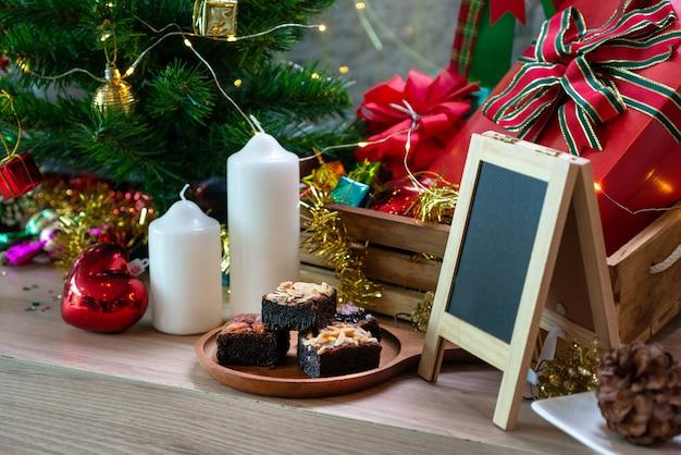 クリスマスの装飾の背景と、木製のテーブルのブラウニーチョコレートケーキ Premium写真