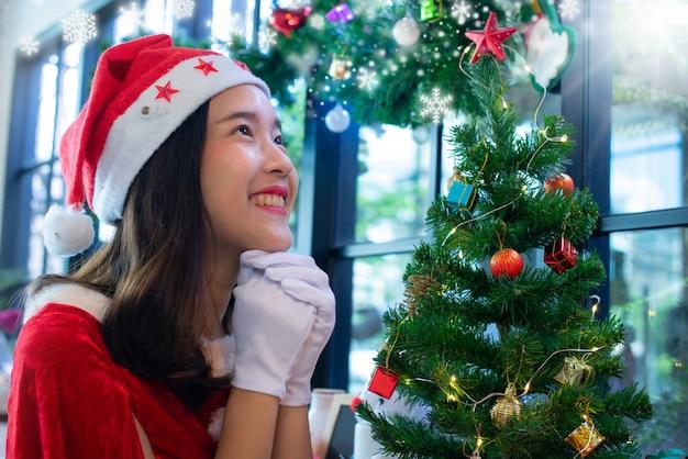 クリスマスの服を着た美しいアジアの女の子、クリスマスのために祈るサンタの帽子クリスマスコンセプト Premium写真