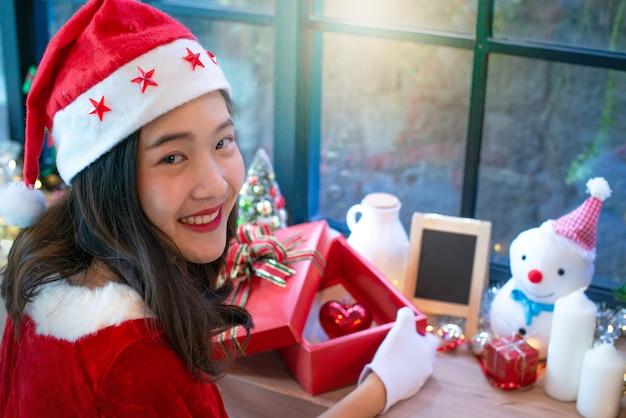 美しいアジアの女の子、クリスマスを着て、サンタの帽子、開いたギフトボックス、赤い心のボックス Premium写真