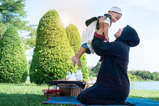 幸せな幸せなアジアのイスラム教徒の母親は、空気の中で彼女の息子を投げる、イスラム教徒のお母さんと息子の概念 Premium写真