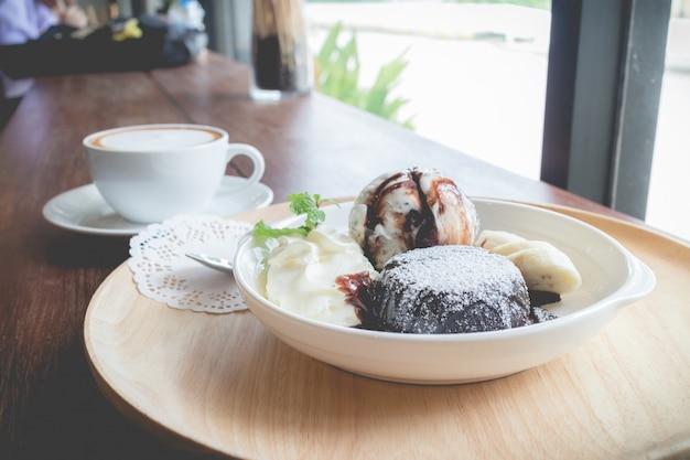 バニラアイスクリームボール、バナナ、ホイップクリームの入ったホットチョコレート溶岩ケーキ Premium写真