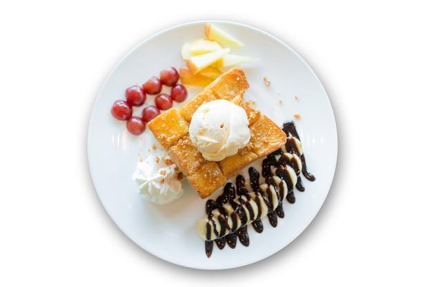 Медовый тост с ванильным мороженым, взбитыми сливками и шоколадным сиропом Premium Фотографии