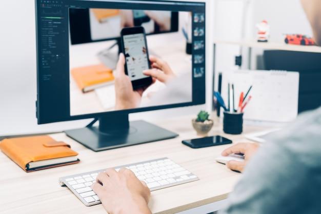 Молодой человек, работающий редактирование стилей фотографий на экране компьютера компьютера дома, бизнес фотографии Premium Фотографии