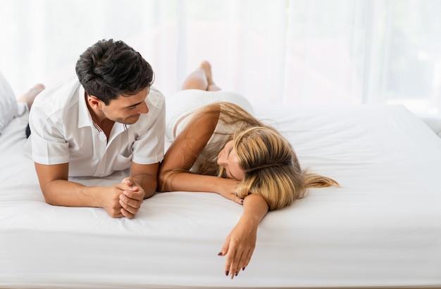 早朝にベッドの上に敷設白人カップルの恋人 Premium写真