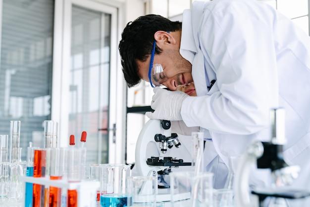 健康と医学の研究をしながら顕微鏡検査実験を通して見る科学者 Premium写真