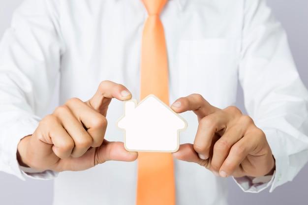 木製のカットハウスの形、隔離された背景を保持するビジネスマンの手 Premium写真