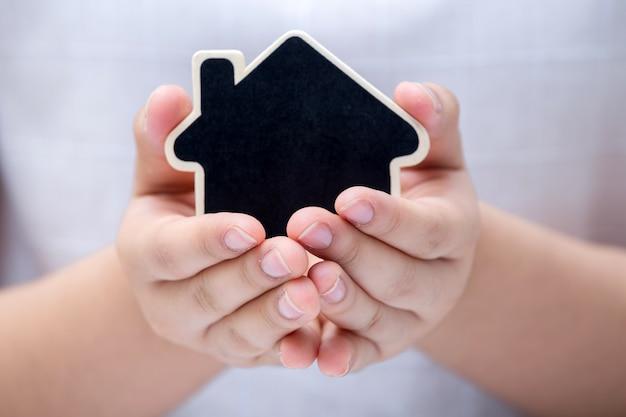 小さい家を持っている女性。不動産ビジネスのコンセプト。 Premium写真