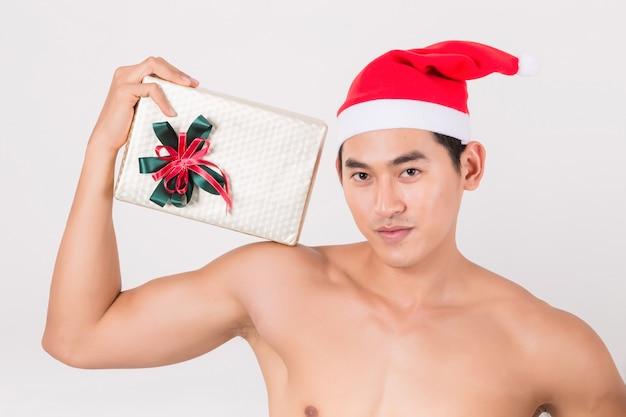 セクシーな若い男と彼のギフトボックスを保持している赤いサンタクロースの帽子の服。 Premium写真