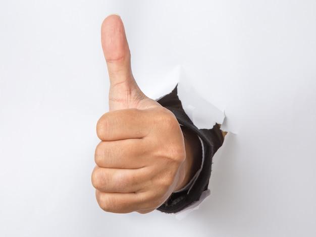 Мужская рука с большим пальцем вверх жестом пробивая бумагу Premium Фотографии