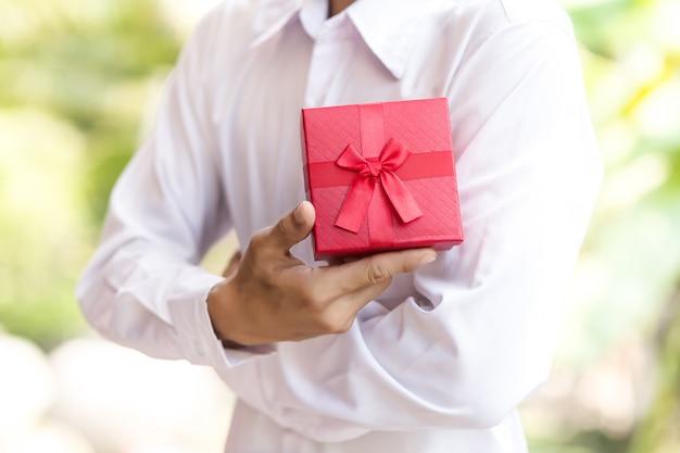 ビジネスの男性は手に赤いギフトボックスを保持します。 Premium写真