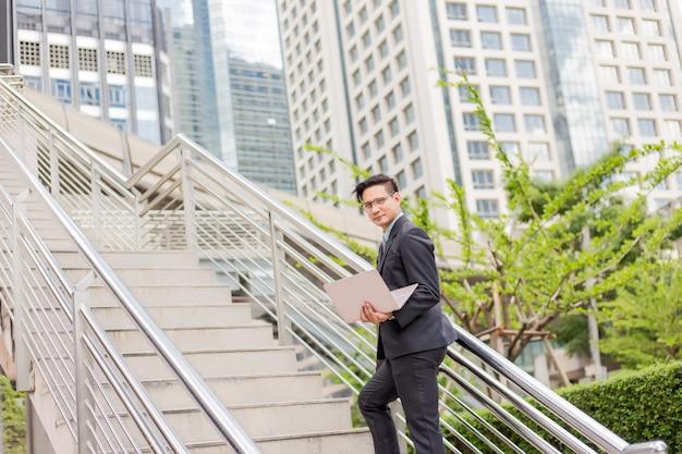 仕事にラッシュアワーに階段を上る彼のラップトップを持つビジネス男 Premium写真