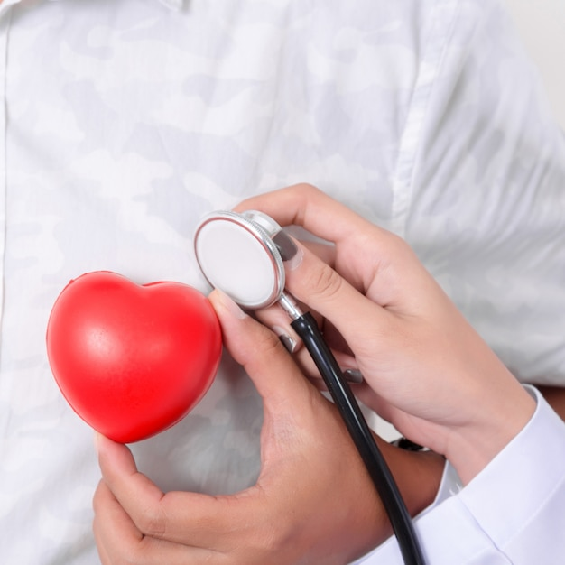 医者は心電図ラインと聴診器で赤いハートをチェックします。 Premium写真