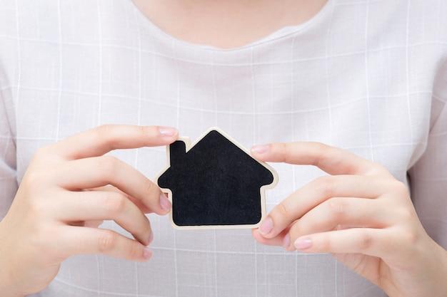 小さな家を持つ女性。不動産事業のコンセプトです。 Premium写真