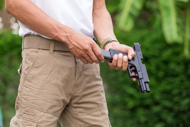 Человек в грузовых штанах с пистолетом Premium Фотографии
