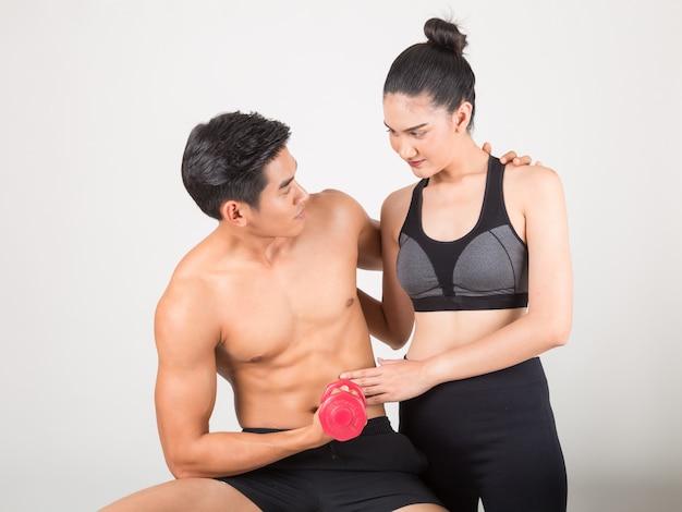 幸せな若いフィットネス男と訓練時間の彼のガールフレンド。フィットネスや健康的なライフスタイルのコンセプト。スタジオ撮影白い背景の上。 Premium写真