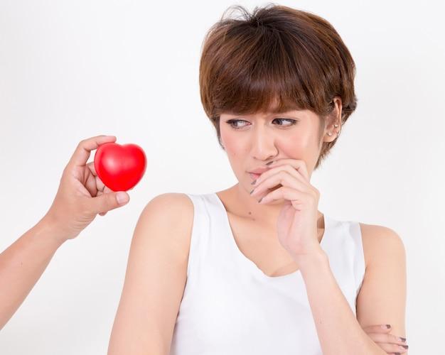 失望した女性は彼女のボーイフレンドの赤いハートを拒否しました。白い背景に分離されました。スタジオの照明 Premium写真
