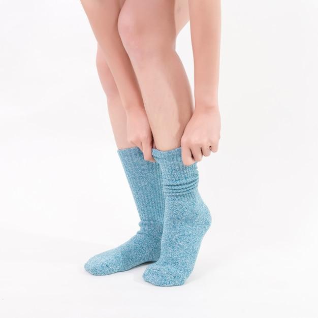 美しい女性の足に青い綿の靴下。白い背景に分離されました。スタジオ照明 Premium写真