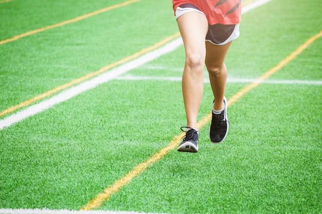スポーツ分野で走っている若いスポーツ少女 Premium写真