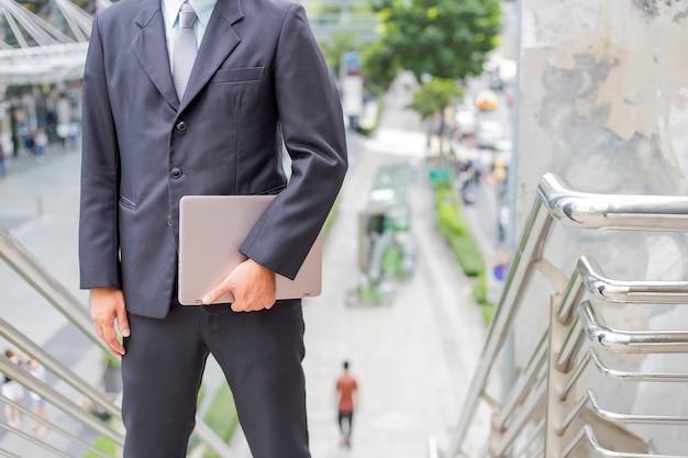 仕事にラッシュアワーに階段を上る彼のラップトップを持つビジネスマン。急いでください。 Premium写真