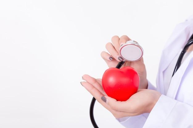 Доктор проверяя красное сердце с линией и стетоскопом экг. концепция для здоровых Premium Фотографии