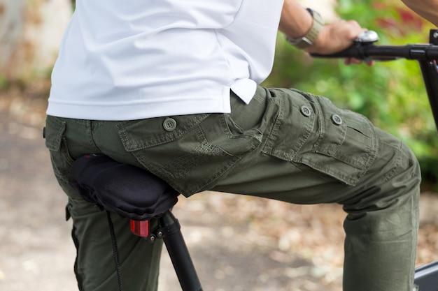 庭で自転車に乗ってカーゴパンツを持つ男 Premium写真