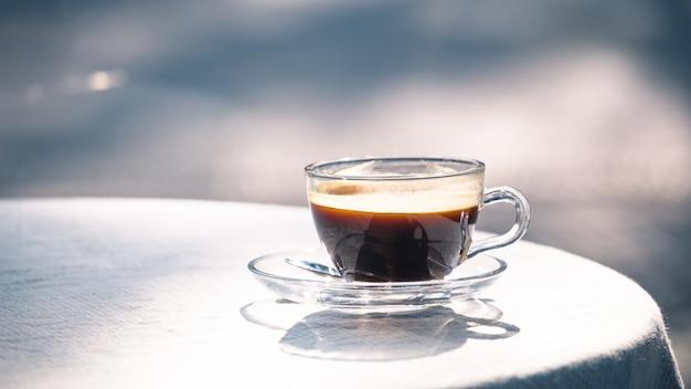 テーブルの上のブラックコーヒーのホットカップ Premium写真