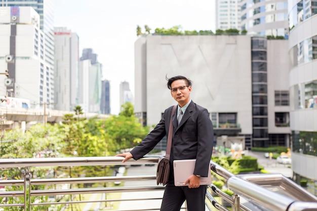 屋外の彼のラップトップコンピューターとの訴訟で若いアジア系のビジネスマン Premium写真