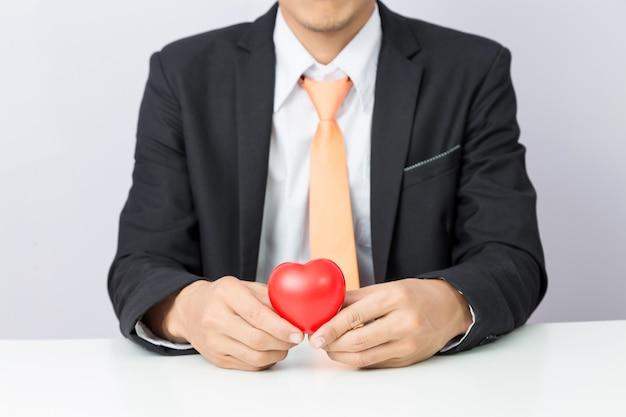 ビジネスマンは赤いハート、孤立した背景を保持します。 Premium写真